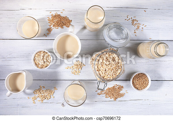 Set of different glass containers with oat milk, oat seeds and flakes on white wooden table. - csp70696172