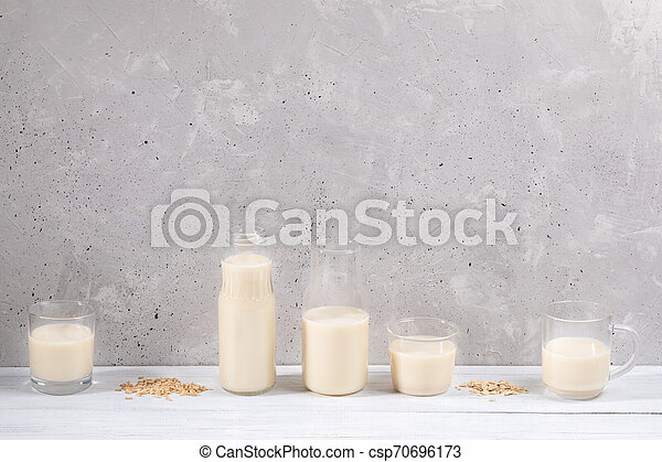 Set of glass containers with oat milk on white wooden table on concrete wall background. - csp70696173