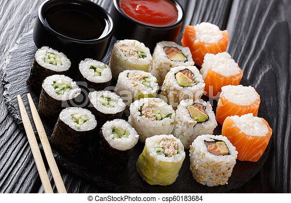 set of tasty Japanese rolls closeup with sauces on a stone. horizontal - csp60183684