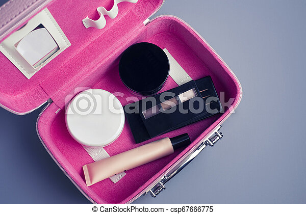 Set of woman's cosmetics in a bag. Women's secrets. Cosmetics, perfume, brushes, powder, highlighter, concealer, patelle with eye shadows. female cosmetics bag on white background. Make up. Copy space - csp67666775