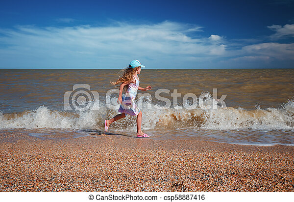 Seven years old girl in summer dress running along the sea at sunny day - csp58887416