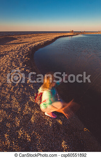 Seven years old girl on the beach at sunset time - csp60551892
