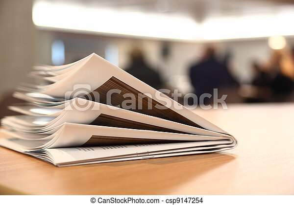 several brochures on light table in bright room, brochures are folded twice - csp9147254