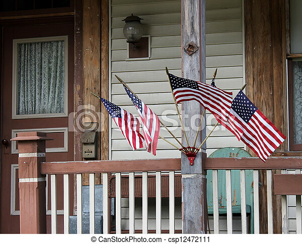 Several flags on old rural porch - csp12472111