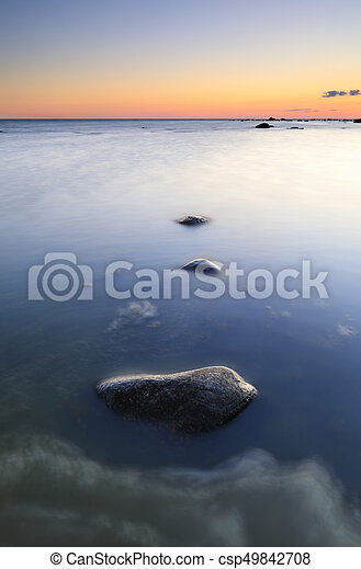 Several rocks in quiet sea at sunset - csp49842708