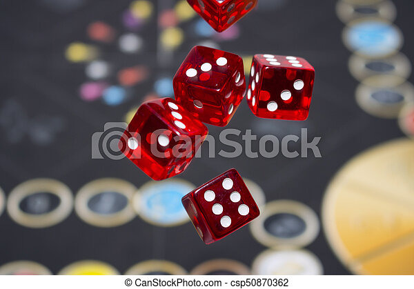 Several rolling red dice fall on a table with boardgame. Gameplay moments - csp50870362