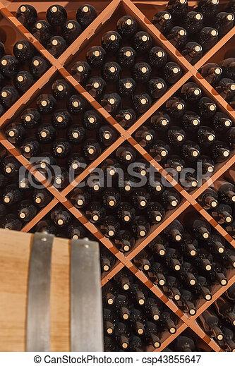 Several Varietal Wine Bottles and Barrel Age Inside Cellar - csp43855647