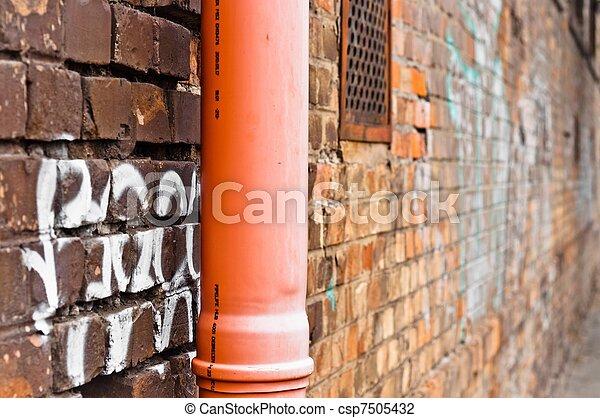 Sewage pipe on brick abandoned wall - csp7505432