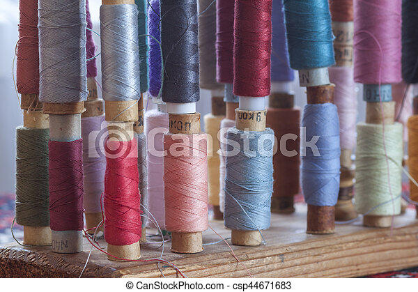 Sewing multicolored threads of soft pastel vintage colors on spools. Sewing tailor related accessories. - csp44671683