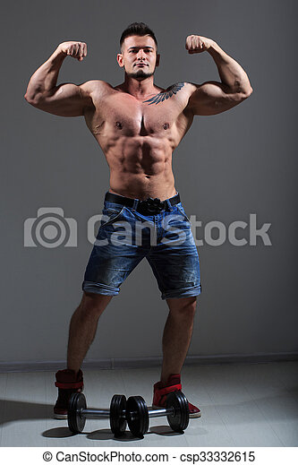 sexy athlete in denim shorts. with dumbbells - csp33332615
