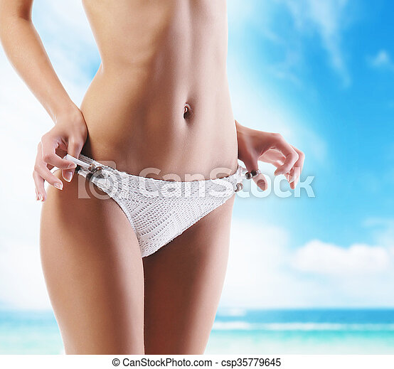 ed49b1112 Sexy body of a young and fit woman on a resort background - csp35779645