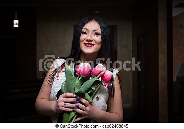 Sexy brunette stands with flowers - csp62468845