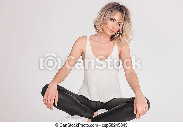 Sexy Casual Woman Wearing Leather Pants Sitting With Legs Crossed Csp58245843