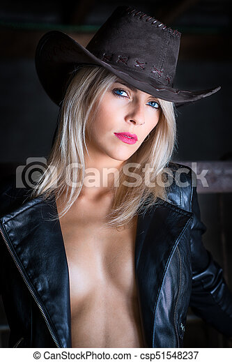 Sexy country girl wearing cowboy hat and leather jacket - portrait in a  barn. 1372dc481bd