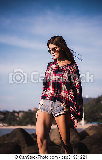 Sexy Girl in flannel shirt on the rocky beach. - csp51331221