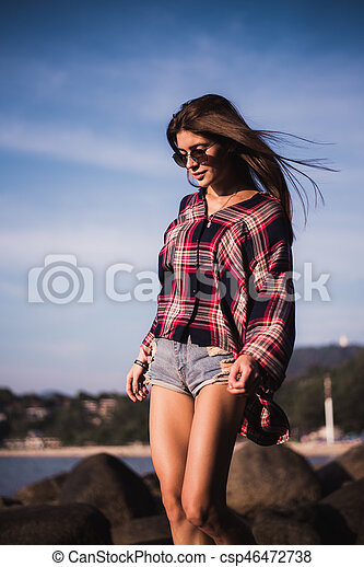 Sexy Girl in flannel shirt on the rocky beach. - csp46472738