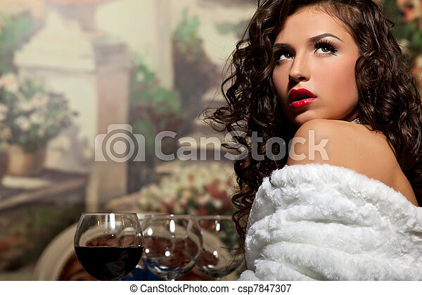 Sexy girl sit with wine in fur coat at evening - csp7847307
