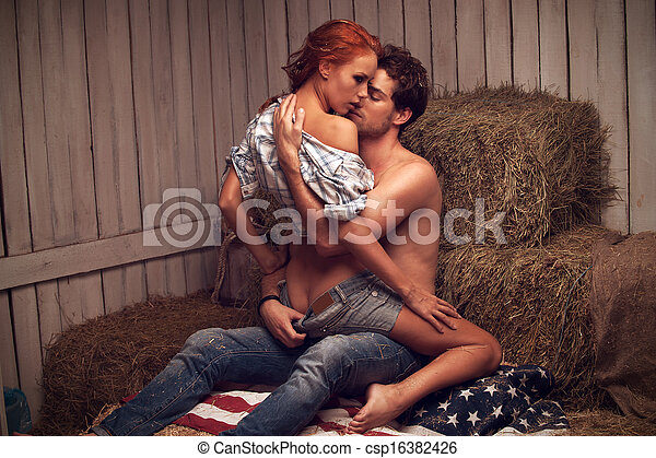 Sexy man kissing beautiful woman. Sitting in hayloft - csp16382426