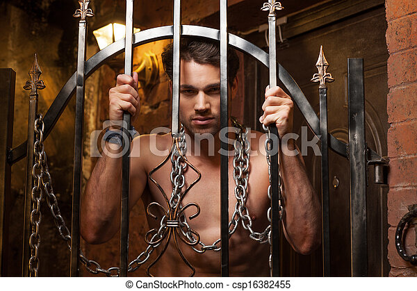 Sexy man standing behind metal gates. With metal chain on neck  - csp16382455