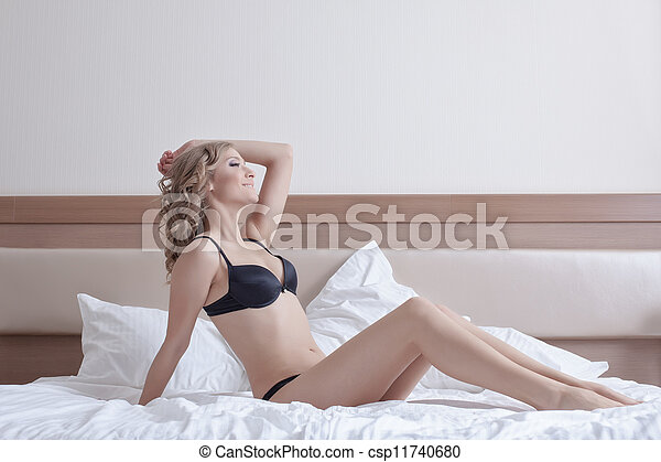 sexy woman posing in black lingerie on hotel bed - csp11740680