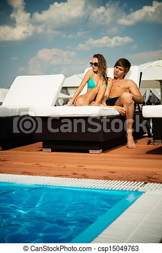 Couple Sexy Plage sexy young couple relaxing near pool on a beach bed .