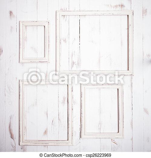 Shabby chic frames. Shabby chic white frames on wooden wall.