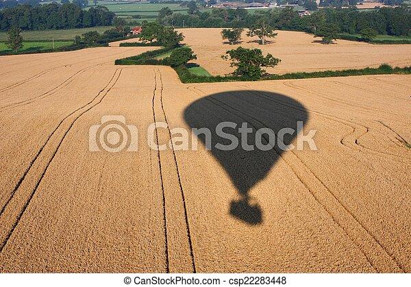 Shadow of a hot air balloon flying over rural farmland - csp22283448