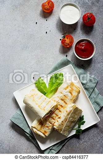 Shawarma pita bread with grilled chicken, shaurma doner, fresh vegetables and cream sauce on a light stone or concrete background. Top view with copy space, concept restaurant fast food. - csp84416377