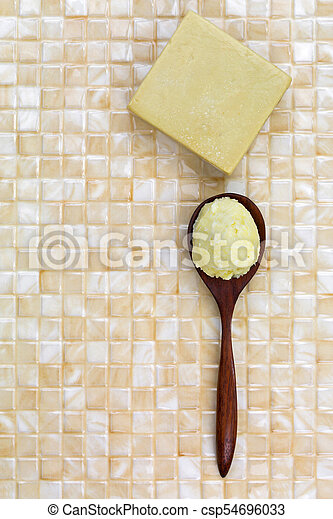 Shea butter in wooden spoon, homemade olive oil soap on yellow tile background - csp54696033