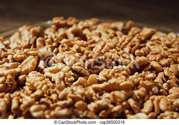 shelled walnuts on a plate, wooden background - csp36500316