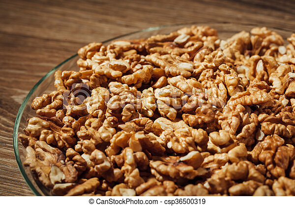 shelled walnuts on a plate, wooden background - csp36500319