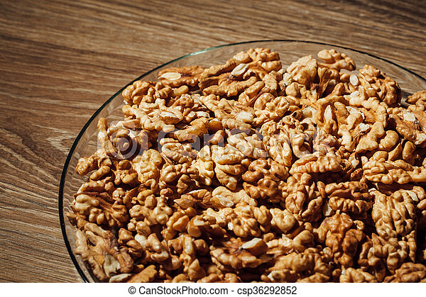 shelled walnuts on a plate, wooden background - csp36292852