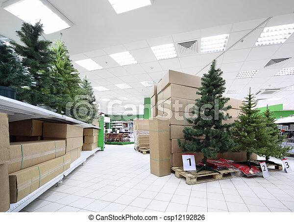 Shelves with variety of artificial Christmas tree inside large supermarket - csp12192826