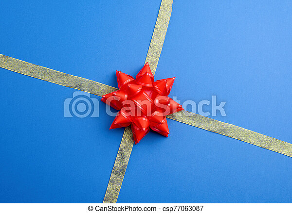 shiny golden silk ribbon crossed on a blue background in the middle of a red bow - csp77063087