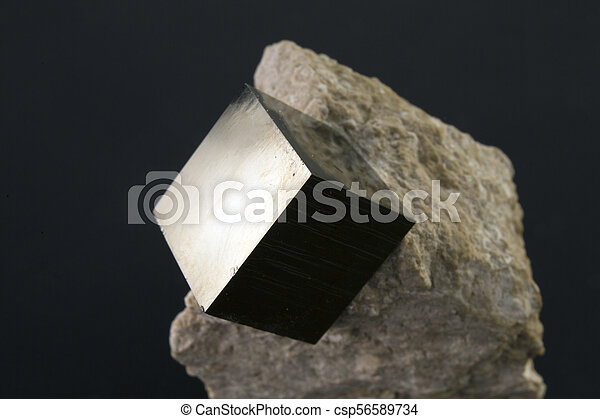 Shiny smooth regular shape pyrite cube on a dark background - csp56589734
