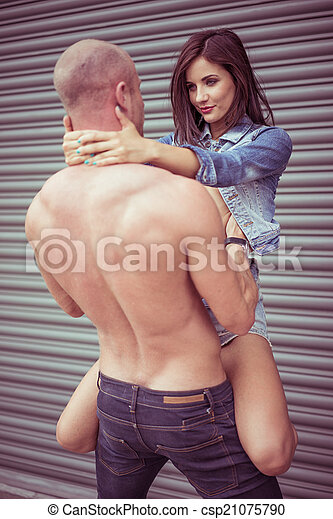 Shirtless man carrying female model - csp21075790