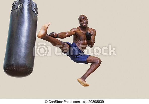 Shirtless muscular boxer kicking punching bag - csp20898839