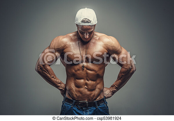 58d8a370 Shirtless muscular guy in blue jeans and white cap. isolated on grey  background.