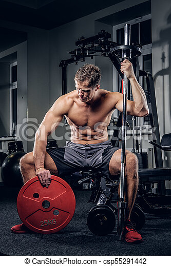 shirtless muscular male in a gym club shirtless muscular