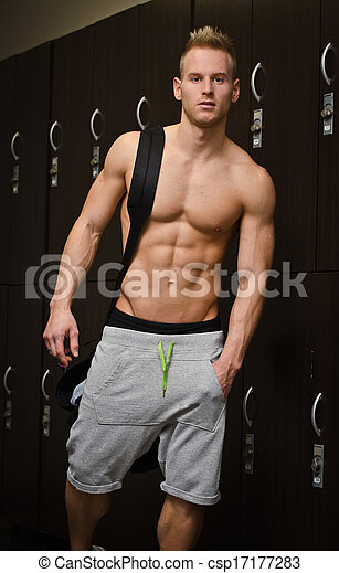 Shirtless muscular young male athlete in gym dressing room - csp17177283