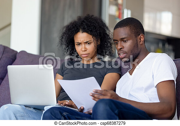 Shocked African American couple receiving bad news, reading letter - csp68387279