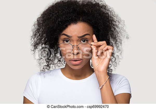 Shocked african young woman lowering glasses looking at camera - csp69992470