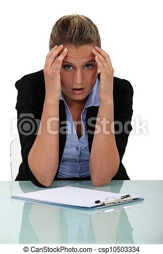 Shocked employee sitting at her desk - csp10503334