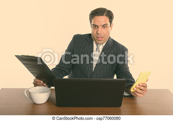 Shocked Persian businessman holding mobile phone and clipboard while using laptop on wooden table - csp77060080
