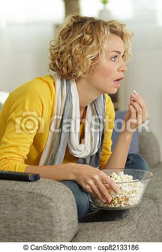 shocked woman at home watching something on tv - csp82133186