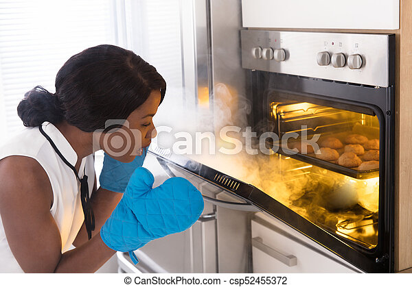 Shocked Woman Looking At Burnt Cookies In Oven - csp52455372