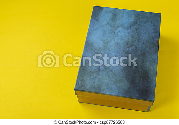 Shoe box in blue on a yellow background. - csp87726563