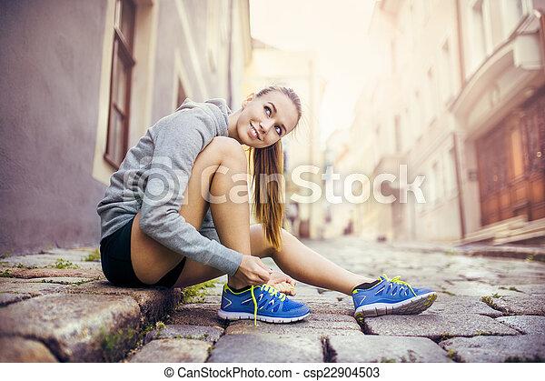 Una joven corredora atando sus zapatos - csp22904503