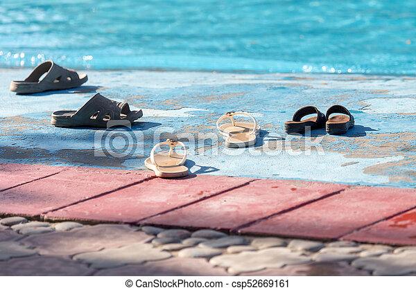 Zapatos junto a la piscina - csp52669161