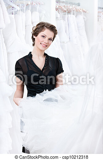 Shop assistant try to select a proper dress for the client - csp10212318